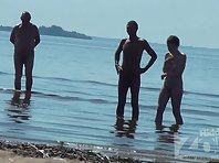 Nu1478# Summer nudists like to relax on the beach. They do not know that they are being watched Nu