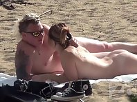 Nu2188# A man and a woman are sunbathing on the beach. They chose a secluded place where no one woul