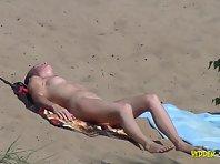 Nu1060# A slender young woman lying sunbathing on a nudist beach