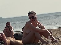 Nu1349# Back in the spotlight of a nude beach voyeur camera a woman with big boobs. We can watch h