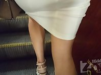 Up2960# Under the skirt of a brunette in a tight white dress. The girl stood with her legs wide apar