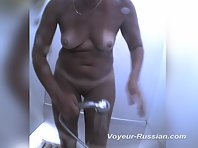 Pv600# A woman in a black bathing suit undressed and takes a shower. Our cameraman, from behind the