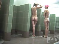 Sh1980# Three women take a shower. They soap their bodies and then wash off the foam under running w