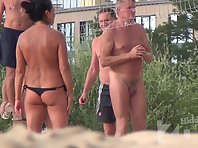 Nu2031# Nudists play on the beach in volleyball. Some men are completely naked, topless girls. Their