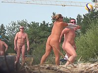 Nu2037# On a nudist beach, everyone will find something to their liking. someone is playing ball, so