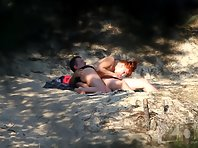 Nu1959# A couple sunbathing on the sand. Suddenly the redhead begins to suck her friend's cock. She