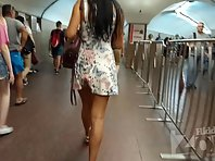 Up2780# Under the skirt of a tanned brunette in a short white dress. Beautiful tanned legs and shave