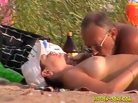 Nu1133# A man with glasses caresses his girlfriend on a nudist beach. He kisses her nipples and st