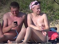 Nu2157# A young couple came to the nudist beach. They undressed and sat on the sand. The girl has a