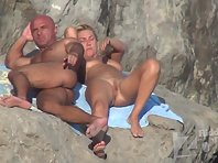 Nu2236# A couple sunbathes on the rocks. The woman lies with her legs spread wide, we can clearly se