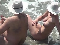 Nu1875# A pair of nudists relax in the sea waves. The girl has a beautiful big chest. A man is strok